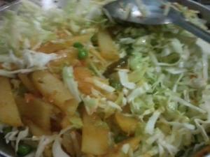 Adding cabbage in potato and peas